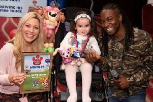 Naomi Wilkinson and Nigel Clarke present three-year-old Kaysey with her award for courage