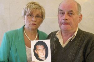 Briege Quinn and Stephen Quinn hold a photo of their murdered son Paul.