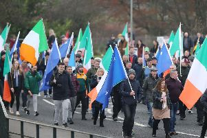 People take part in an Irish unity march as they cross the Lifford Bridge, from Donegal, which marks the border between Strabane in County Tyrone, Northern Ireland, and Lifford in County Donegal in the Republic of Ireland