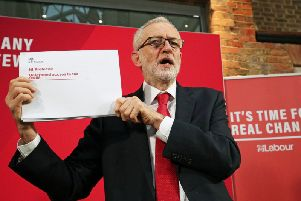 Labour Party leader Jeremy Corbyn holds up a leaked document relating to Northern Ireland, during a press conference in central London, whilst on the General Election campaign trail. (Photo: Jonathan Brady/PA Wire)