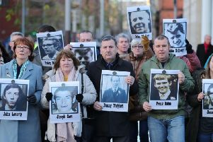 Family members outside Laganside Courts in Belfast hold images of some of those who were killed in disputed circumstances over the course of three days between August 9-August 11, 1971