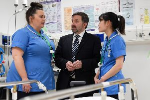 Health Minister Robin Swann talks with staff nurses Amber Loung (right) and Gillian Browne during a visit to the Ulster Hospital at Dundonald