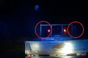 A still from Rugby Police's dash cam video, showing two occupants of the 4x4 throwing bricks.