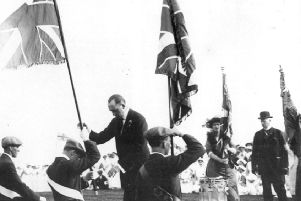 Edward Carson presents 'colours' to the Ulster Volunteer Force in 1912. The uniforms are leggings, flat caps and a variety of belts. In the background are white-robed volunteer nurses.