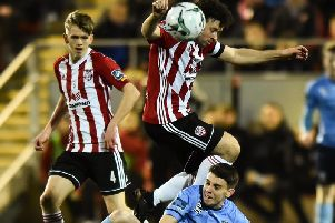 Ciaran Harkin watches on as Derry City skipper, Barry McNamee evades a challenge from Gary O'Neill.