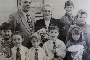 May McRoberts, who has retired after 28 years' service at Ballyclare Primary School, pictured with principal Winston Pollock and pupils who presented her with gifts. 1997