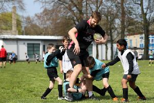 Pupils at Edenderry Primary tackle Ulster star Iain Henderson during a Kingspan Coaching Masterclass at the school in Portadown