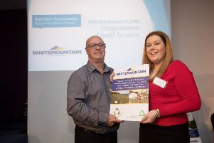 George Thompson from Rathfern Community Regeneration Group receives the funding award from Whitemountain's communications officer Niamh-Anne McNally.