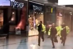 Videograb taken with permission from the twitter feed of @GrizzleMarine showing police running through the Arndale Centre in Manchester where at least four people have been treated after a stabbing incident. (Photo: P.A. Wire)
