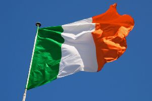 Irish flag fluttering in a brisk breeze against a bright blue sky. PPP-180731-140201006