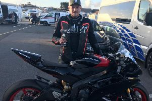 Nick Whitcher clutches his third place trophy alongside his bike