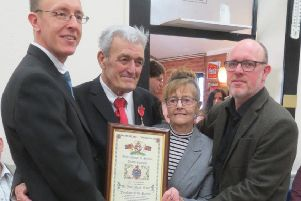 John Monk MBE and his wife Maureen, alongside sons Andrew (left) and David (right), holding the Freedom of the Parish scroll.