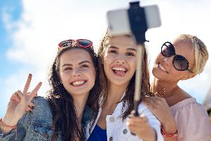 Giggling girls taking a selfie with a selfie stick
