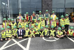 GRAHAM representatives welcome the Carrickfergus Model Primary School party to the site.