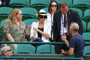 A man, believed to be a royal bodyguard, speaking to a spectator who had taken a selfie as the Duchess of Sussex watches the Serena Williams match on court one during day four of the Wimbledon Championships at the All England Lawn Tennis and Croquet Club, Wimbledon