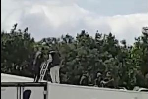 Pictures show men on top of a lorry.
