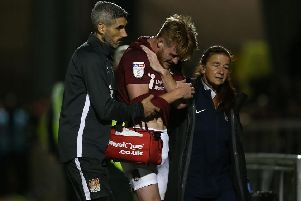 Ryan Watson is helped off the pitch after suffering a broken collarbone in the clash with Peterborough United on Tuesday night