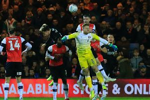 Sonny Bradley heads away from Charlton keeper Dillon Phillips who went up for a late free kick at Kenilworth Road