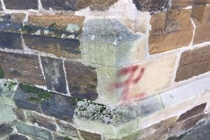 The symbol has been graffitied onto the wall near to the door of the church.