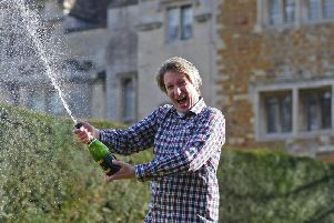 Leigh Hancox celebrates with a bottle of bubbly