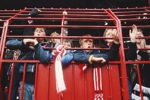 Football fans watching from behind bars during the 1980s