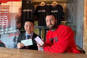 Zien Zhou with Jack Gibson, director of Fitness Worx and the cheque. Photo by Fitness Worx