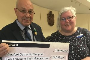 Outgoing chairman of NKDC Geoff Hazelwood presents the cheque from funds raised in his civic year to Sleaford Dementia Support secretary Bex Mezzo. EMN-190517-170057001