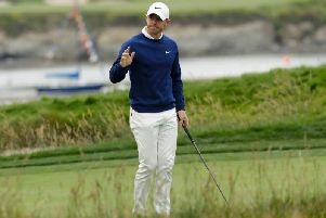 Rory McIlroy, of Northern Ireland, waves after his putt on the 17th hole during the first round of the U.S. Open Championship