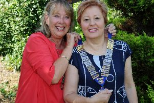 Linda Carvell (left) hands over the inner wheel club chains to Pam Coughlan