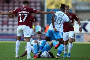 David Sesay of Crawley Town attempts to play the ball away from team mate Jordan Tunnicliffe as Shaun McWilliams of Northampton Town looks on during the Sky Bet League Two match (Photo by Pete Norton/Getty Images)
