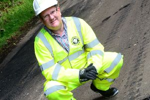 Cllr Mark Shaw pictured next to a pothole