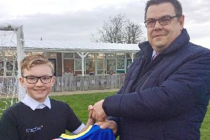 Archie Starsmore, one of the school's Bronze Sports Ambassadors, receives the new sports kit from Julian Welch of Barker Storey Matthews.