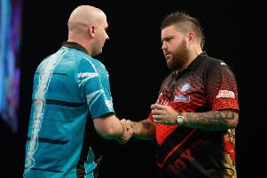 Rob Cross (left) shakes hands with Michael Smith at the end of their match in Aberdeen tonight. Picture courtesy Steve Welsh/PDC