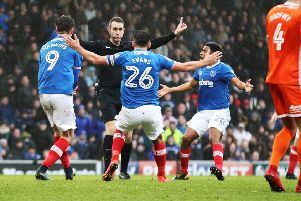 Referee David Coote is surrounded by Portsmouth players.