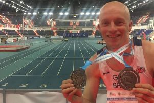 Dave Brown with his two medals at the World Indoor Masters Championships in Poland.