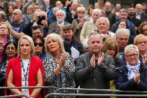 The public outside St. Anne's Cathedral, Belfast, applaud Lyra McKee as her coffin is carried inside.