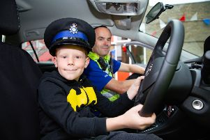 Stanley Snelling (7) tries out a police hat and car for size