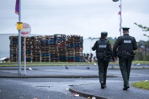 Two PSNI officers walking towards the 11th night bonfire at Avoniel Leisure Centre, after a statement was read out by a Belfast City Council worker from inside a PSNI vehicle requesting that people on council property vacate the area. Belfast City Council reaffirmed its decision yesterday for the third time, to remove materials from a bonfire site beside the centre. Pic by Liam McBurney/PA Wire