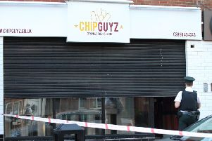 A fast food outlet was cordoned off after the shooting in the Springfield Road area