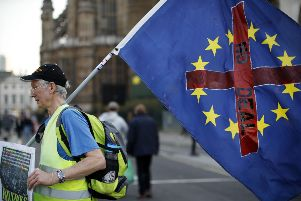 "A demonstrator carries a flag as he walks near the Houses of Parliament in central London on March 29, 2019. - British MPs on Friday rejected Prime Minister Theresa May's deal for leaving the European Union for a third time, raising the spectre of a ""no deal"" exit or a long delay to the process. (Photo by Tolga AKMEN / AFP)        (Photo credit should read TOLGA AKMEN/AFP/Getty Images) YPN-190208-142533060"