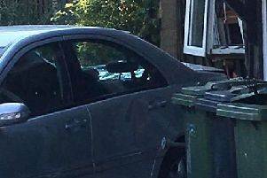 A car is reported to have reversed into the house
