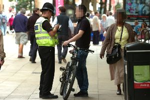 A cyclist is booked by a Police officer for riding along Bridge street during a campaign to reduce the number of cyclists ignoring no cycling signs ENGEMN00120110729165641