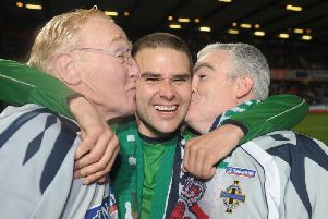 David Healy gets a kiss from Northern Ireland team attendants Terry Hayes and the late, Derek McKinley during a Euro 2008 qualifier against Denmark at Windsor Park in Belfast.