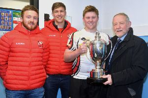 Armagh captain, Aaron Whyte receives the trophy from Brian Irwin, chairman of the tournament sponsors, Irwin's Bakery. Also included are Ulster payers David Busby, left, and Caleb Montgomery.