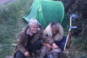 The couple and their dog Biggy sitting in front of the green tent that has been stolen.