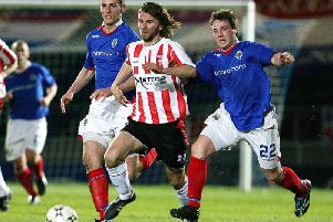 Derry City's Paddy McCourt races away from Linfield pair Oran Kearney and Jamie Mulgrew.