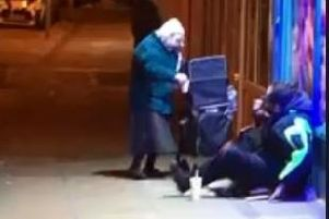 This was the moment an elderly woman was recorded handing out food to those on the street. She has since become an internet sensation. Photo: Charlie Franks