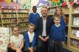 Head teacher, James Hartley, alongside some of the children of Victory Primary School.