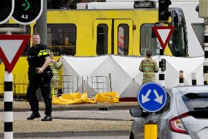 """Rescue workers install a screen on the spot where a body was covered with a white blanket following a shooting in Utrecht, Netherlands, Monday, March 18, 2019. Police in the central Dutch city of Utrecht say on Twitter that """"multiple"""" people have been injured as a result of a shooting in a tram in a residential neighborhood. (AP Photo/Peter Dejong)"""