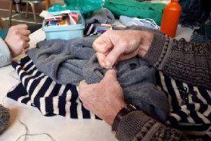 A jumper is fixed up at Repair Caf Portsmouth